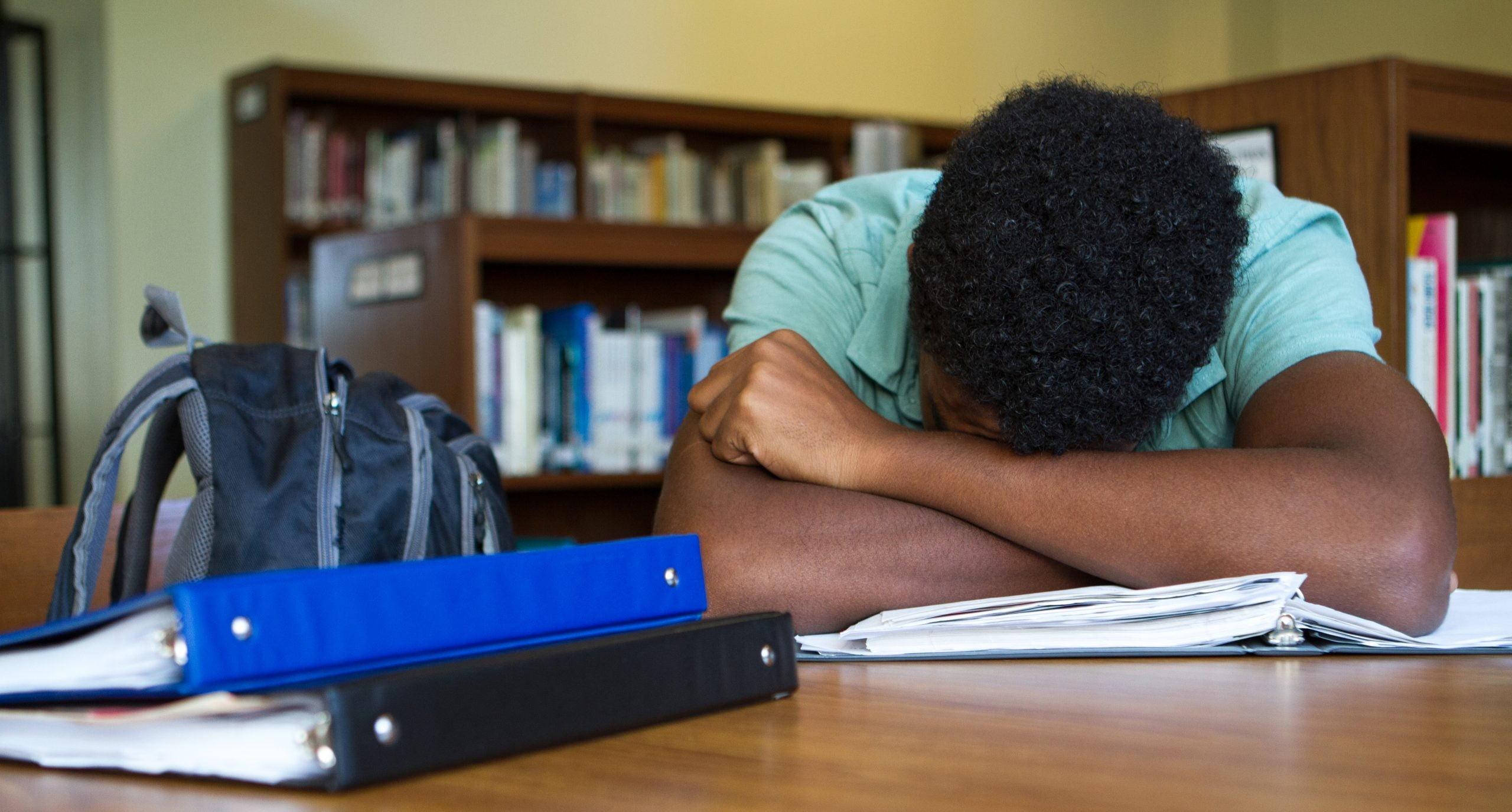 Foto de um jovem negro em uma biblioteca. Ele está de cabeça baixa, apoiada entre os braços, em uma mesa de madeira.