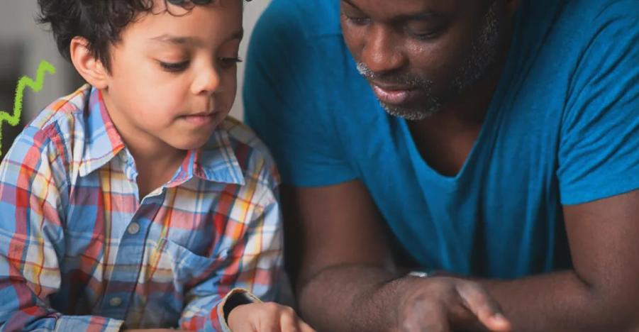 Foto de um menino e um homem negro que estão juntos, lado a lado, lendo um livro.