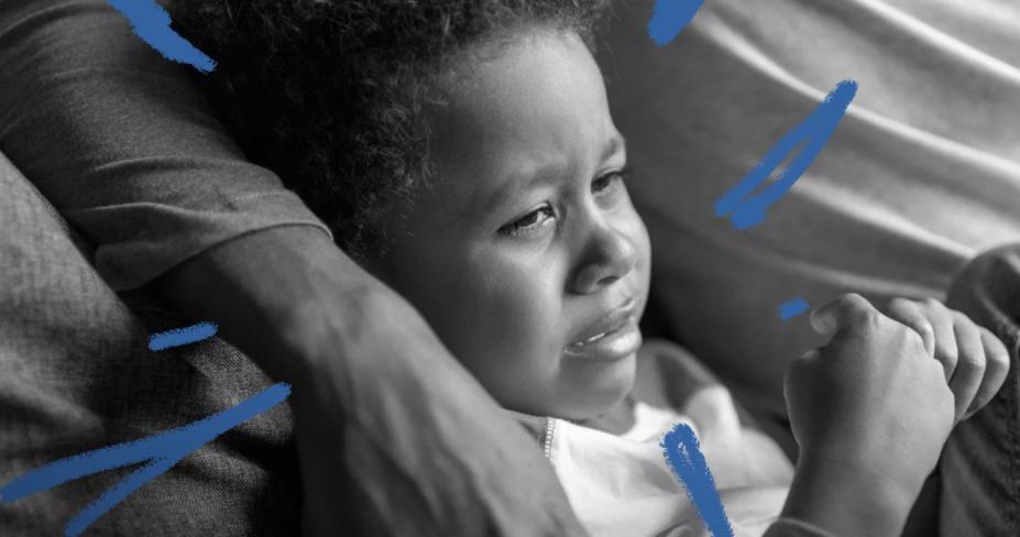 Foto em preto e branco de um menino negro chorando nos braços de um adulto.