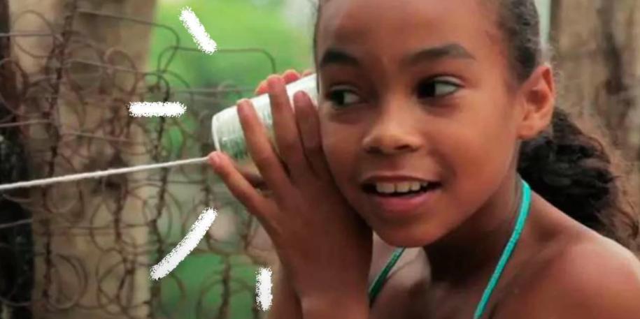 Foto de uma menina negra brincando de telefone de lata. Ao fundo, algumas árvores e uma mata verde aberta.