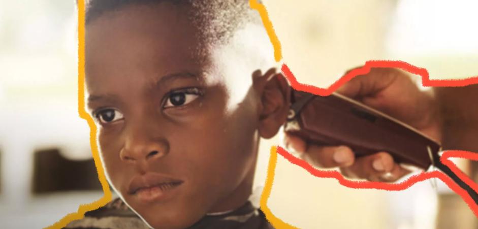 Foto de um menino negro olhando para a frente, sério. Ele está sentado e um cabeleireiro corta seu cabelo com uma máquina.