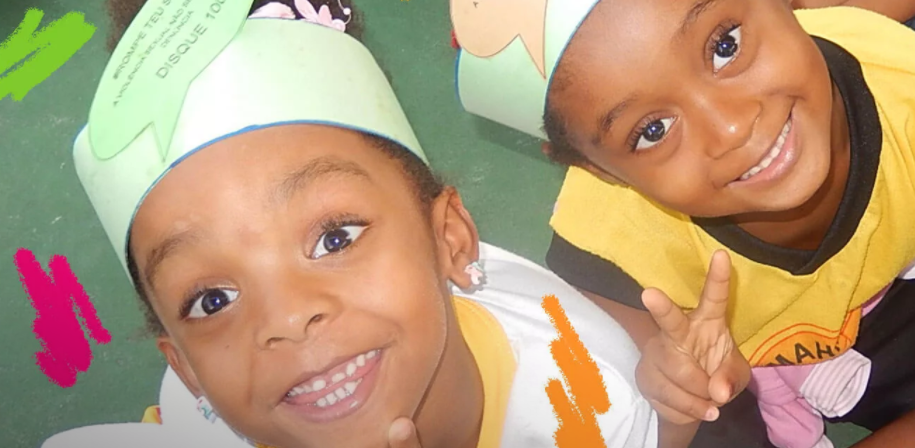 Foto de duas meninas negras. Elas estão sentadas no chão, de pernas cruzadas, e sorriem.