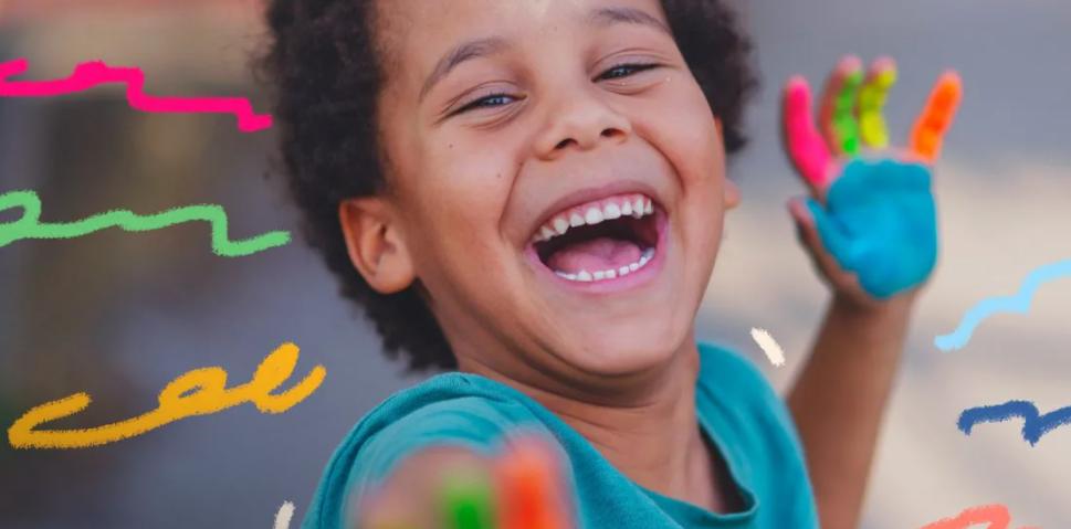 Foto de um menino negro sorrindo e olhando para a ccâmera. As palmas de suas mãos estão pintadas com tinta colorida.