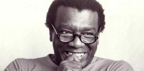 Foto em preto e branco de Milton Santos, um homem negro que usa óculos e sorri. Ele veste uma camiseta.