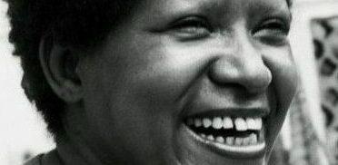 Foto em preto e branco de Lélia Gonzalez, uma mulher negra e de cabelos curtos e crespos. Ela sorri.