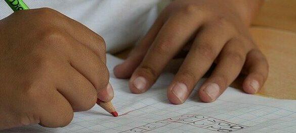 Foto da mão de uma criança, que usa um lápis de cor para fazer um exercício de matemática.