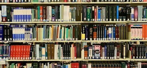 Foto colorida de uma estante lotada de livros de diferentes tamanhos e formatos.