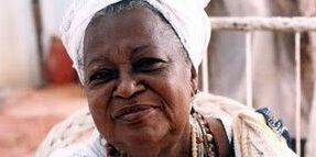 Foto de Mãe Beata, uma mulher negra, que sorri e olha para a foto.