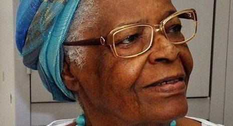 Na foto, Mãe Stella de Oxóssi. Ela é uma mulher negra, usa um turbante azul e óculos de armação quadrada.