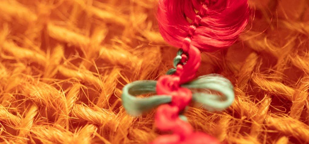 Foto em zoom de um tecido e fios trançados na cor laranja, verde e rosa.