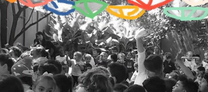Foto em preto e branco de muitas crianças reunidas em um pátio.