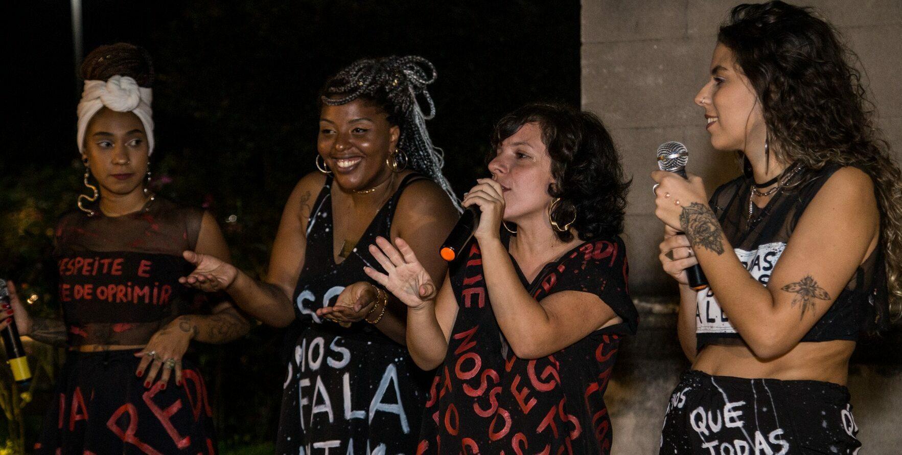 Na foto, quatro mulheres participam de um slam. Uma delas segura um microfone.
